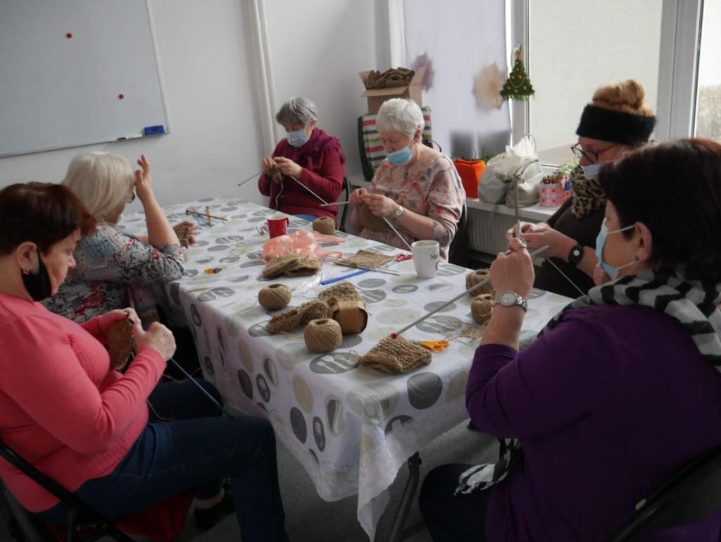 kobiety siedzą i robią na drutach myjki ze sznurka konopnego